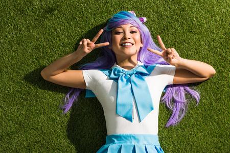 Sonriente chica anime asiática tumbado en la hierba y mostrando signos de paz