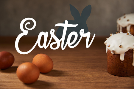 selective focus of traditional Easter cakes and chicken eggs on wooden table with easter lettering Stock Photo