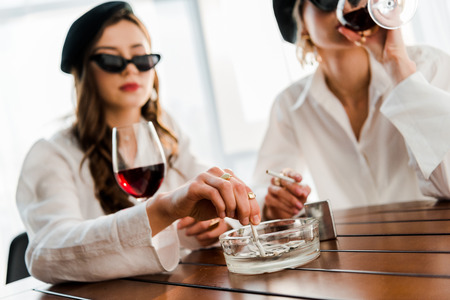 selective focus of brunette and blonde women in black berets and sunglasses drinking red wine and smoking cigarettes together