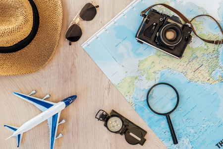 Top view of film camera, straw hat, compass, toy plane, magnifier, sunglasses and world map on wooden surface