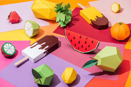 origami ice cream and handmade cardboard fruits on multicolored paper Stock Photo