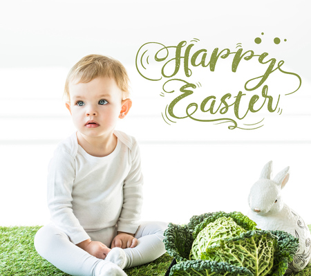 child sitting near savoy cabbage and decorative bunny on green grass with green happy Easter lettering Stock Photo