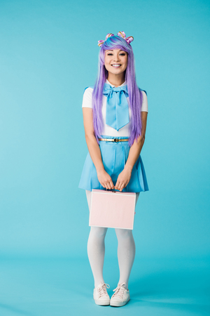 Full length view of anime girl in purple wig holding briefcase on blue background