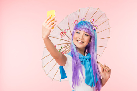 Smiling Asian anime girl with paper umbrella taking selfie isolated on pink background
