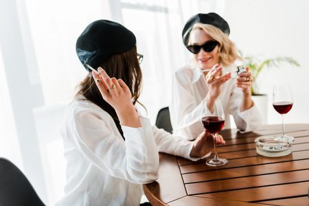 Brunette and blonde women in black berets and sunglasses drinking red wine, talking and smoking cigarettes