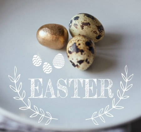 Close up of quill eggs with one painted golden on white plate with Easter illustration