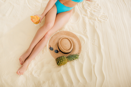 Top view of girl in bikini with cocktail, straw hat, pineapple and sunglasses relaxing on beach 스톡 콘텐츠