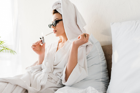 Stylish woman in bathrobe and sunglasses, towel and jewelry lighting up cigarette in bed