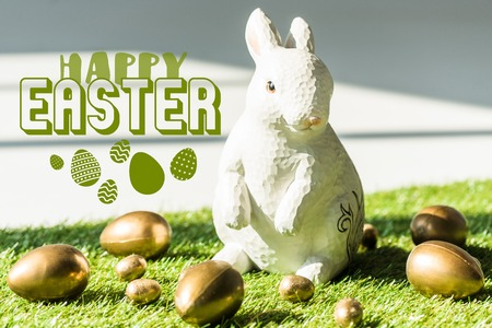 Decorative rabbit on green grass near golden chicken and quail eggs with happy Easter illustration Stock Photo