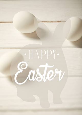 Chicken eggs on white wooden table with happy Easter lettering and bunny illustration Standard-Bild - 121432210