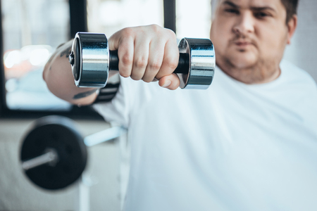 Cropped view of Overweight man looking at camera while training with dumbbell at gym Stock Photo