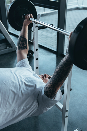 Overweight tattooed man training with barbell at gym Stock Photo