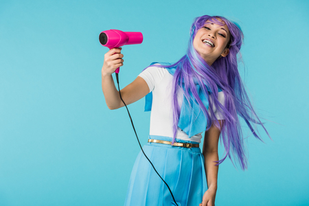 Smiling asian anime girl in wig using hairdryer isolated on blue