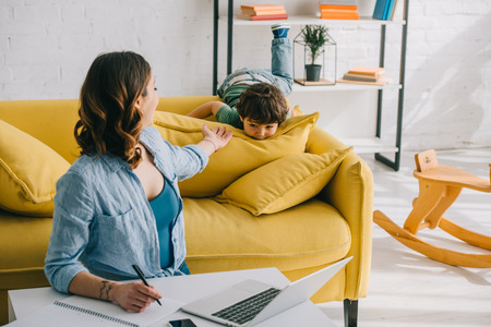 woman looking at son while working with laptop in living room