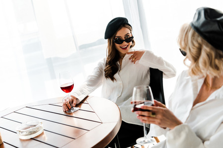 elegant smiling and surprised brunette woman in black beret and sunglasses drinking red wine at wooden table with blonde friend 스톡 콘텐츠