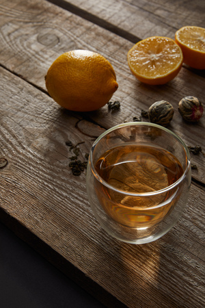 glass of traditional chinese blooming tea and lemons on wooden table