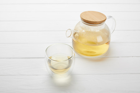 teapot and glass with organic herbal tea on white wooden table