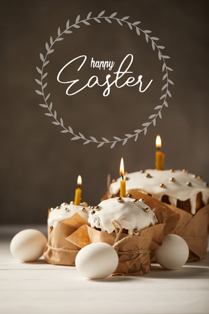 traditional Easter cakes with burning candles and white chicken eggs on brown background with happy easter lettering Stock Photo