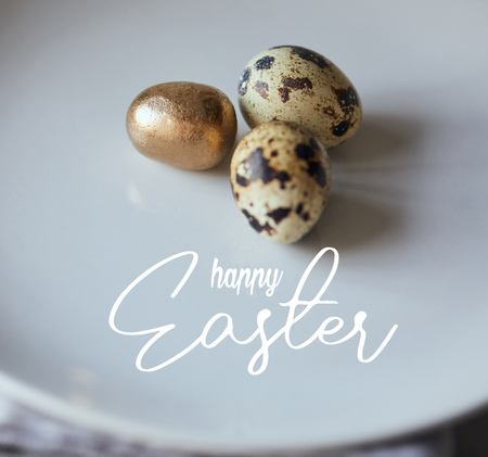 close up of quail eggs with one painted golden on white plate with happy Easter lettering