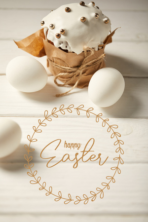 traditional Easter cake and white chicken eggs on white wooden table with happy easter lettering 版權商用圖片