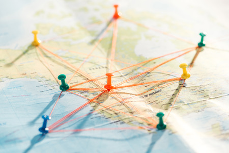 Selective focus of colorful push pins and strings on world map