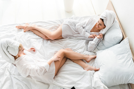 top view of happy barefoot women in jewelry with towels on heads lying in white bed