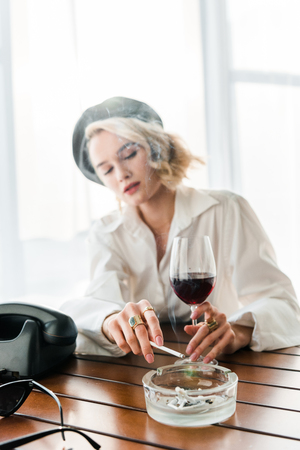 selective focus of elegant blonde woman in black beret smoking cigarette and holding glass with red wine