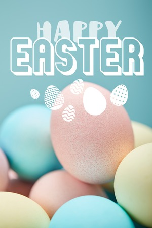 pile of multicolored painted chicken eggs with white happy Easter lettering on blue background Standard-Bild - 121465970