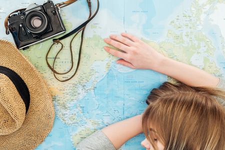 Cropped view of woman with film camera and straw hat sleeping on world map