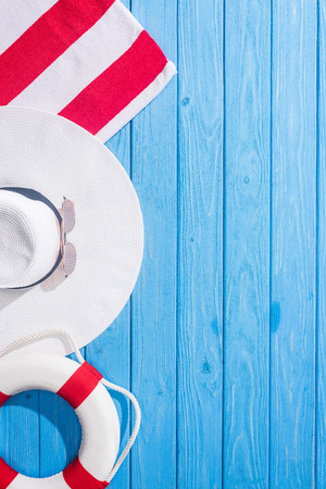 top view of striped towel, white sunglasses, lifebuoy, floppy hat on blue wooden background with copy space Stock Photo