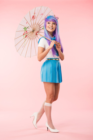 Full length view of smiling asian anime girl holding paper umbrella on pink