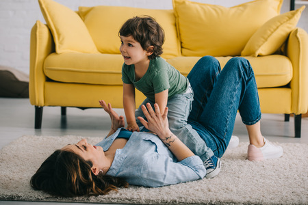 Happy mother and son playing on carpet in living room