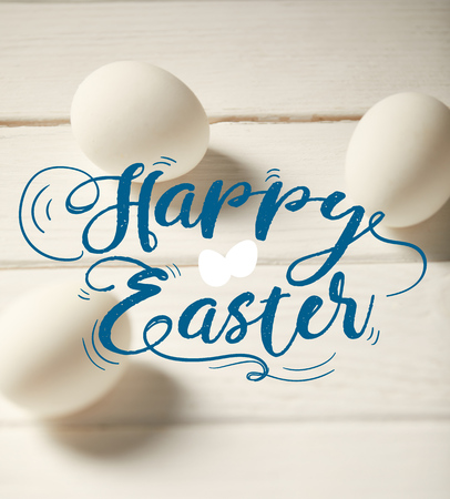 chicken eggs on white wooden table with blue happy Easter lettering