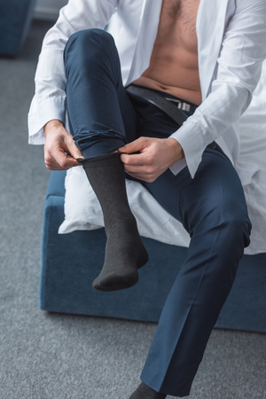cropped view of man sitting on bed and wearing black socks in bedroom