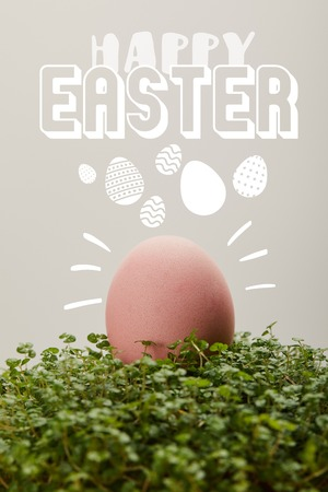pink painted chicken egg on green grass with happy Easter lettering on grey background Standard-Bild - 121467672