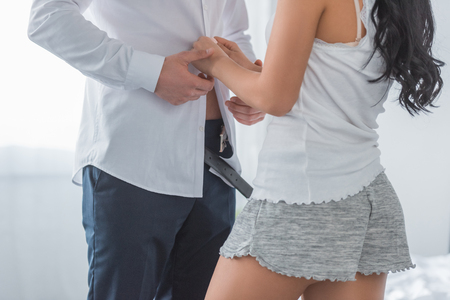 cropped view of brunette young woman touching white shirt on boyfriend standing in bedroom Imagens