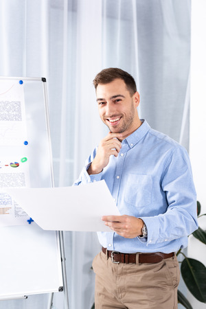 cheerful businessman standing near white board and holding blank paper