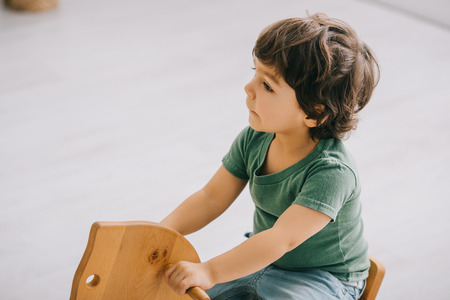 kid sitting on wooden rocking horse in living room