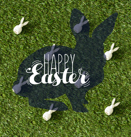 top view of decorative bunnies on green grass with happy Easter lettering