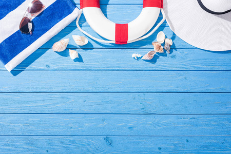 top view of striped towel, sunglasses, lifebuoy, floppy hat and seashells on blue wooden background with copy space