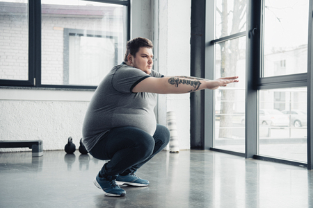 overweight tattooed man doing squats at sports center