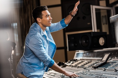 selective focus of smiling mixed race sound producer gesturing while working in recording studio