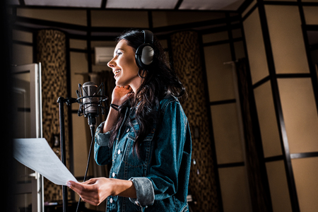 selective focus of pretty woman holding paper with text while singing in recording studio