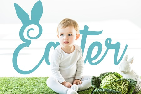 child sitting near savoy cabbage and decorative bunny on green grass with blue Easter lettering Stock Photo