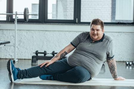 overweight tattooed man looking at camera, smiling and sitting on fitness mat at sports center
