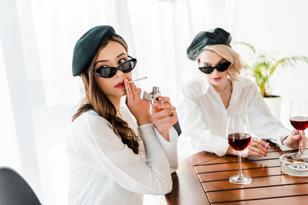 selective focus of elegant woman in black beret and sunglasses lighting up cigarette near friend Stock Photo