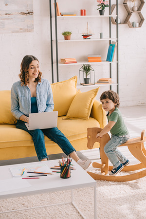 Kid sitting on rocking horse while mother working with laptop in living room