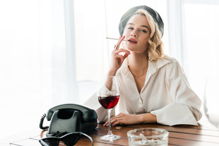 Elegant blonde woman in black beret and white shirt smoking cigarette near glass with red wine and retro telephone Фото со стока