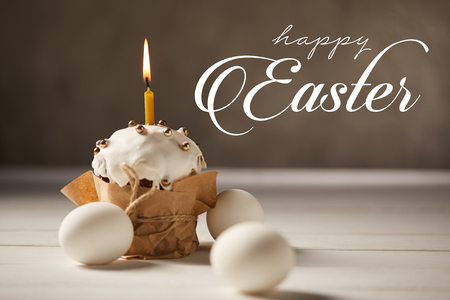 Traditional Easter cake with burning candle and white chicken eggs on brown background with happy Easter lettering Stock Photo