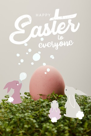Pink painted chicken egg on green grass with happy Easter to everyone lettering and rabbits illustration